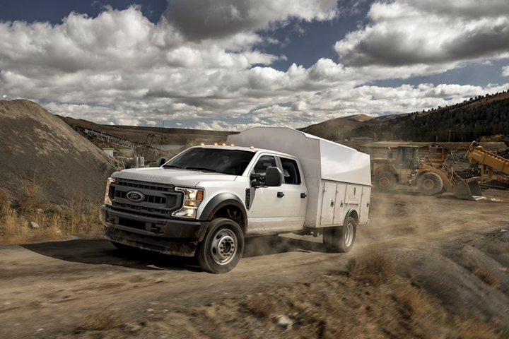 2021 Ford Super Duty Chassis Cab F 4 50 X L in Oxford White being driven on dirt path near construction vehicles