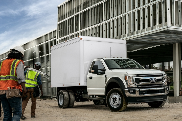 Construction workers carrying materials towards 2021 Ford Super Duty Chassis Cab X L T shown in Oxford White with box truck upfit at worksite