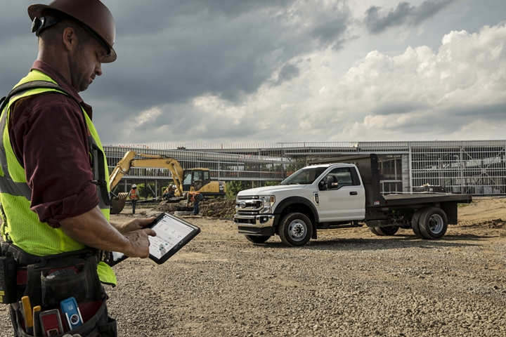 2021 Ford Super Duty Chassis Cab X L T shown in Oxford White with flatbed upfit at construction site