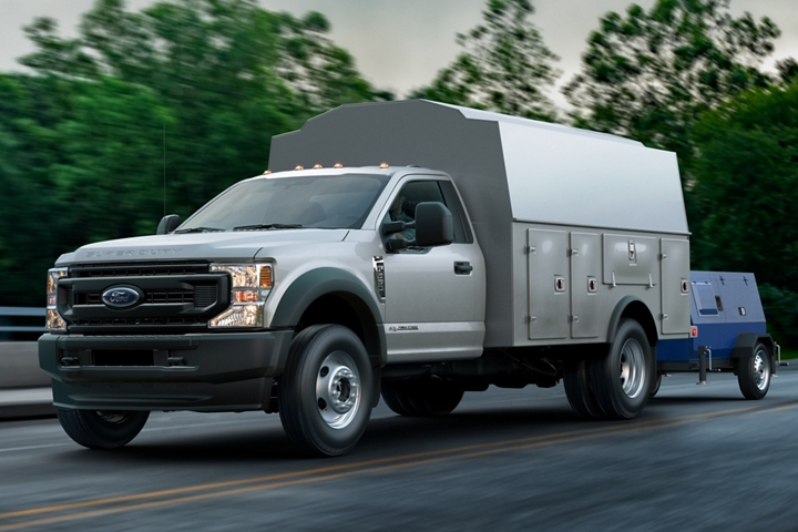 2021 Ford Super Duty F 5 50 X L in Oxford White with upfit being driven on road near trees