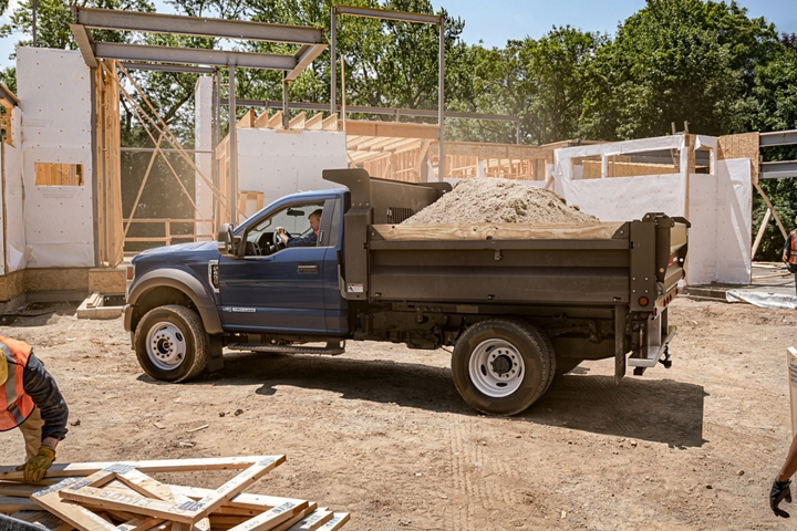 2021 Ford Super Duty Chassis Cab F 600 in Antimatter Blue with upfit carrying dirt at construction site