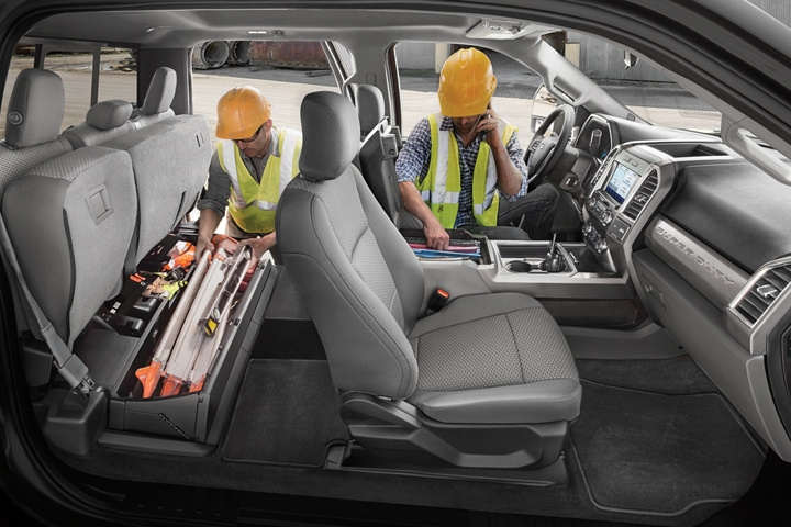 Workers reaching into storage of 2021 Ford Super Duty Chassis Cab X L T interior in Medium Earth Grey