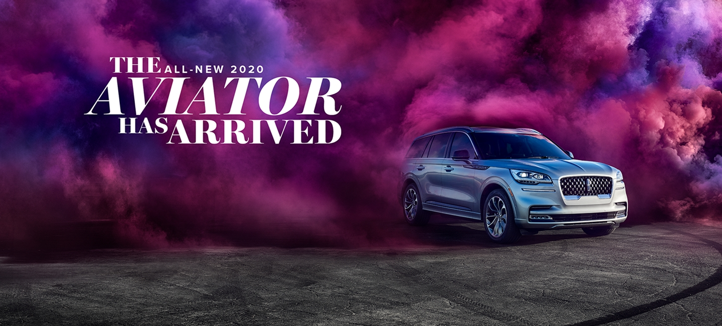 A silver 2020 Aviator emerges from a thick cloud of magenta-coloured smoke. Text reads the all new 2020 Lincoln Aviator has arrived.