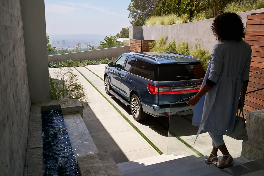 A woman outside a loft approaches a 2021 Lincoln Navigator as the recognition capabilities of the Personal Profiles system are already engaging