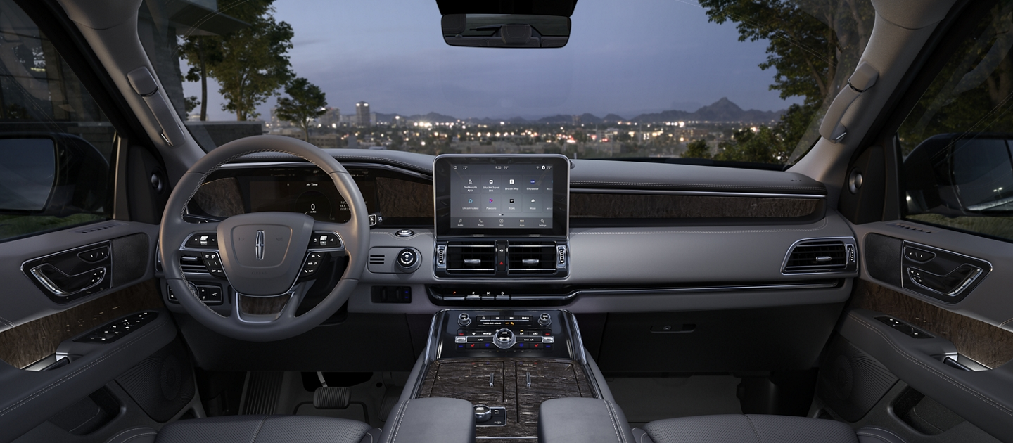 The interior of the front cabin displays a contrast of light greys dark wood and chrome accents with city skyline seen outside the windshield